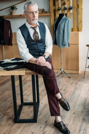 handsome mature tailor sitting on work desk and looking away at sewing workshop