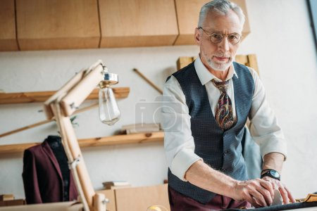 handsome mature tailor marking cloth pattern with chalk at sewing workshop