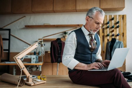 focused mature tailor working with laptop while sitting on table at sewing workshop