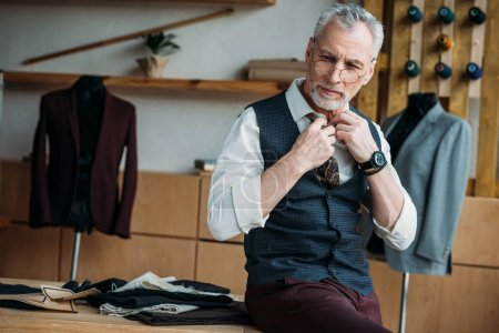handsome mature tailor in stylish clothing sitting on work desk at sewing workshop