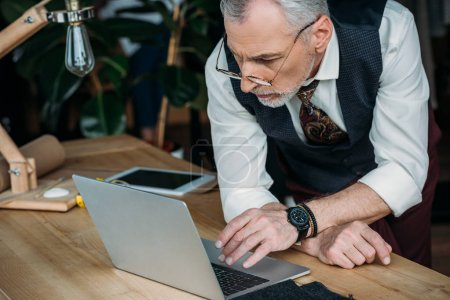 handsome mature businessman working with laptop at office