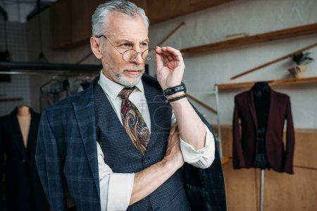 Photo pour Confiant tailleur mature dans des vêtements élégants regardant loin à l'atelier de couture - image libre de droit