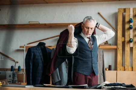 handsome mature tailor putting jacket on shoulders at sewing workshop