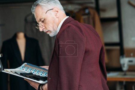 Photo pour Tailleur mature concentré avec catalogue de types de tissu et veste sur les épaules dans l'atelier de couture - image libre de droit