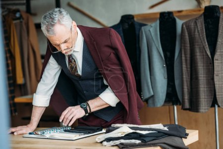 stylish mature tailor with catalogue of cloth types and jacket on shoulders at workplace in sewing workshop
