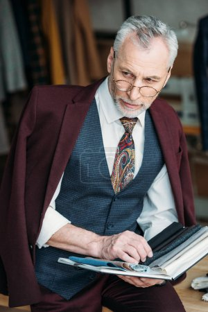 stylish mature tailor with catalogue of cloth types sitting on table at sewing workshop