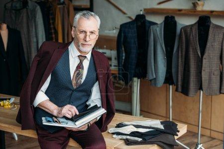 Photo pour Beau tailleur mature avec catalogue des types de tissu assis sur la table à l'atelier de couture - image libre de droit