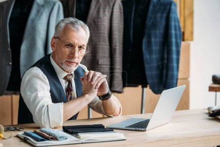 Photo for Serious mature tailor with laptop on work desk at sewing workshop - Royalty Free Image