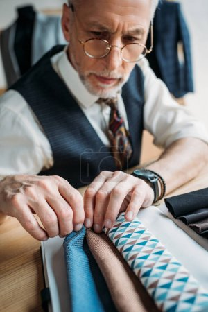 stylish mature tailor looking at cloth samples at sewing workshop