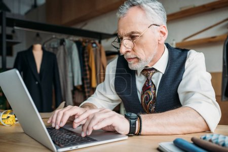 close-up portrait of handsome mature tailor working with laptop at sewing workshop