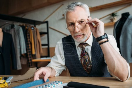 handsome mature tailor with samples of cloth at sewing workshop