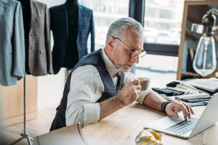 Photo pour Ciblé tailleur mature travaillant avec ordinateur portable et boire du café à l'atelier de couture - image libre de droit
