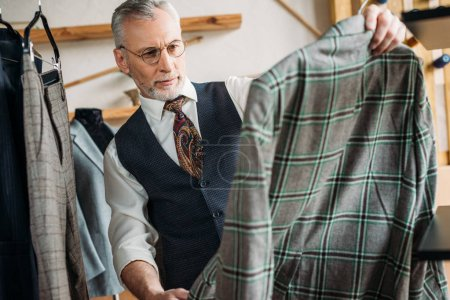 serious mature tailor examining clothes at sewing workshop