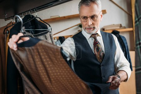 Photo for Handsome mature tailor examining clothes at sewing workshop - Royalty Free Image