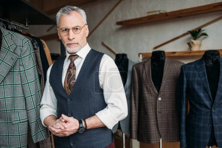 handsome mature tailor looking at camera in sewing workshop