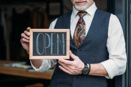 Photo pour Plan recadré de tailleur mature souriant tenant un tableau noir avec panneau ouvert à l'atelier de couture - image libre de droit