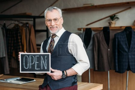 handsome mature tailor holding chalkboard with open sign at sewing workshop