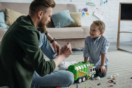 father and little smiling son playing with toy cars together on floor at home