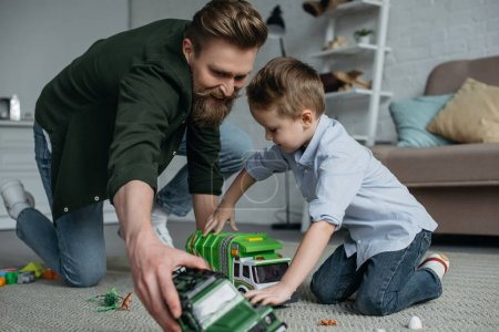smiling father and little son playing with toy cars together on floor at home