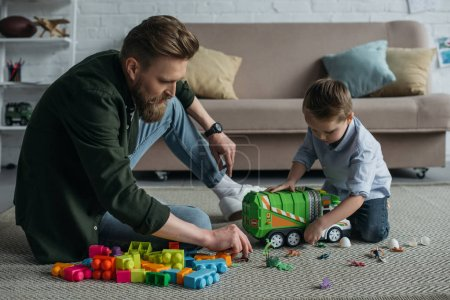 father and little son playing with toy cars together on floor at home