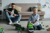 selective focus of father with smartphone and little son with toy cars on floor at home