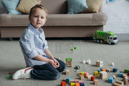 Foto de Vista lateral del niño sentado en el piso con bloques de madera en casa - Imagen libre de derechos