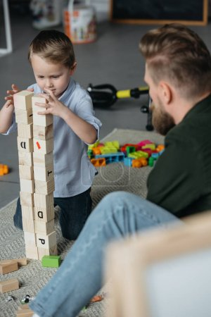 Photo for Selective focus of father and son playing with wooden blocks together at home - Royalty Free Image