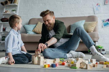 Foto de Feliz padre e hijo jugando con bloques de madera juntos en casa - Imagen libre de derechos