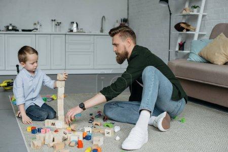 Foto de Padre e hijo jugando con bloques de madera juntos en casa - Imagen libre de derechos