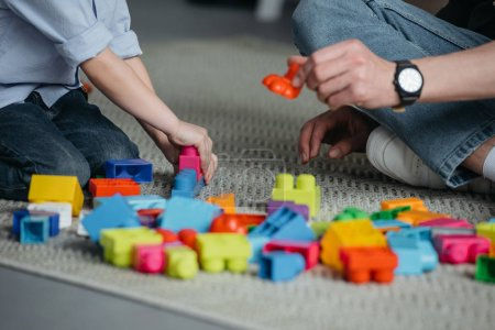partial view of family playing with colorful blocks together at home