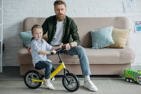 little kid on balance bicycle with bearded father sitting on sofa at home