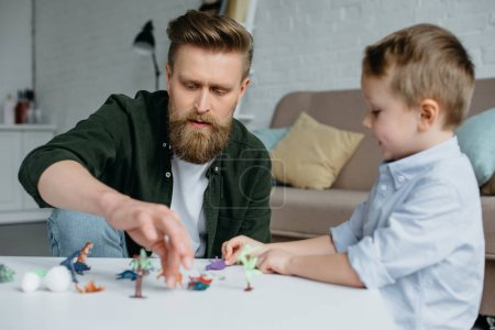 father and cute little son playing with various toy dinosaurs together at home