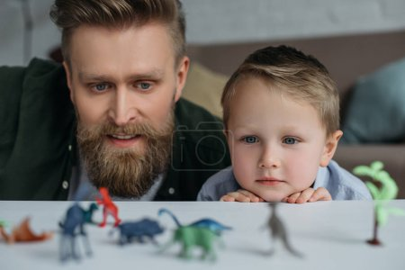 selective focus of father and cute little son looking at arranged toy dinosaurs on tabletop together at home