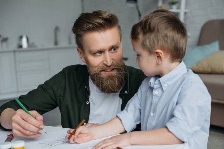 father and cute little son with colorful pencils drawing pictures together at home