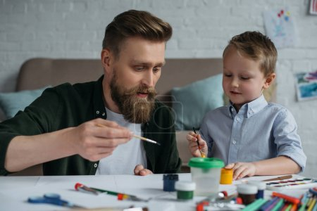 portrait of father and cute little son with paints and brushes drawing pictures together at home