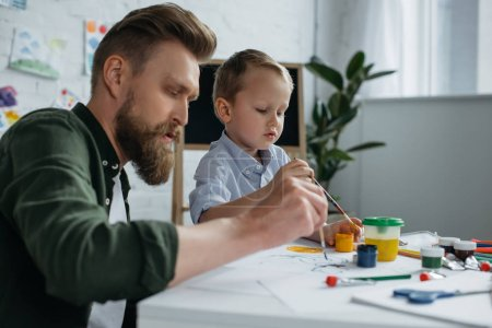 side view of father and cute little son with paints and brushes drawing pictures together at home