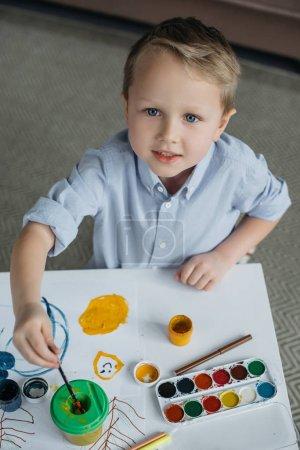 Photo pour Vue de la forte inclinaison du petit garçon avec pinceau et peinture dessin seul à la maison - image libre de droit