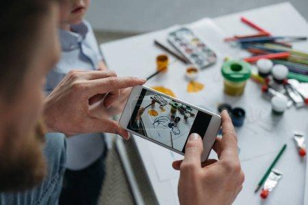Foto de Vista parcial del hombre tomando foto de imagen de hijos en smartphone en el país - Imagen libre de derechos