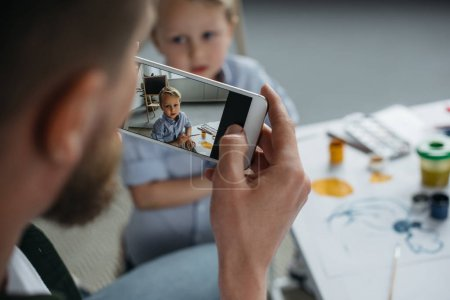 partial view of man taking photo of sons picture on smartphone at home