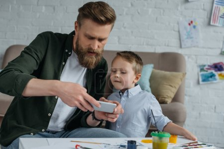 man taking photo of sons picture on smartphone at home