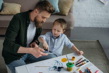 Photo pour Père et petit fils utilisant smartphone ensemble à la maison - image libre de droit