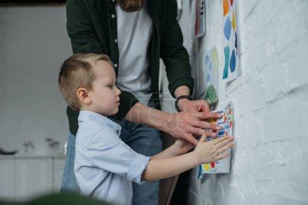 Teilansicht einer Familie, die zu Hause kindische Zeichnung an Wand hängt