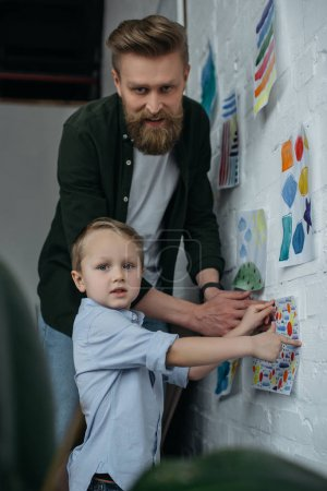 family hanging childish drawing on wall together at home