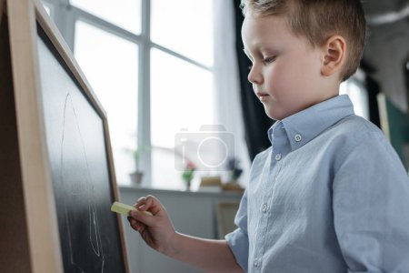 side view of little boy with piece of chalk drawing picture on blackboard at home