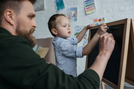 side view of little boy and father with pieces of chalk drawing picture on blackboard at home