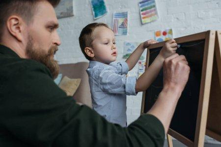 Photo pour Vue latérale du petit garçon et du père avec des morceaux de dessin à la craie sur tableau noir à la maison - image libre de droit