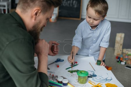 little boy with brush and paints drawing picture together with father at home