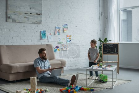 father with laptop sitting on floor with son in room at home