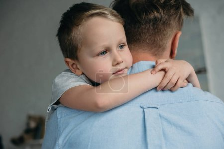 pensive little boy hugging father and looking away at home