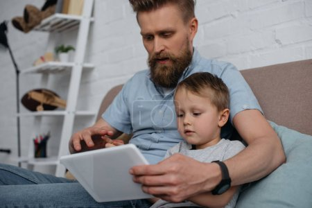 focused father and little son using tablet together on sofa at home